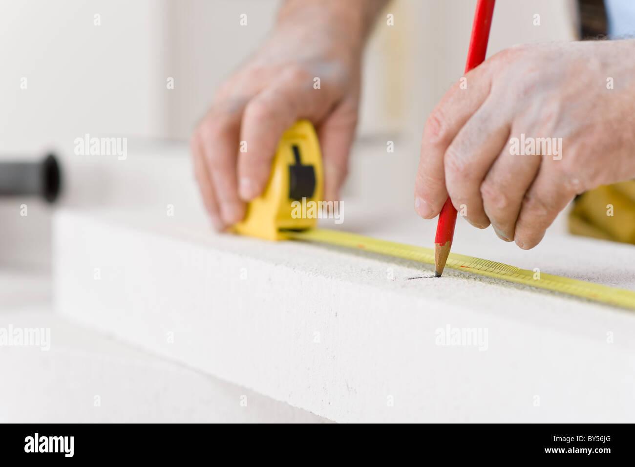 Home improvement - handyman measure porous brick in workshop Stock Photo