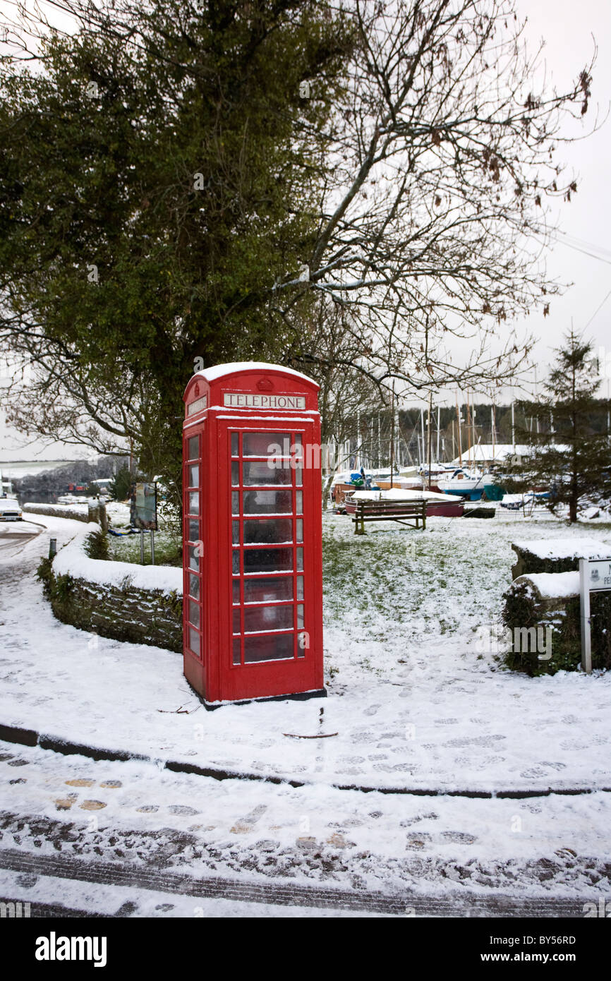 A red telephone kiosk in the snow at Gweek, Cornwall - Stock Image