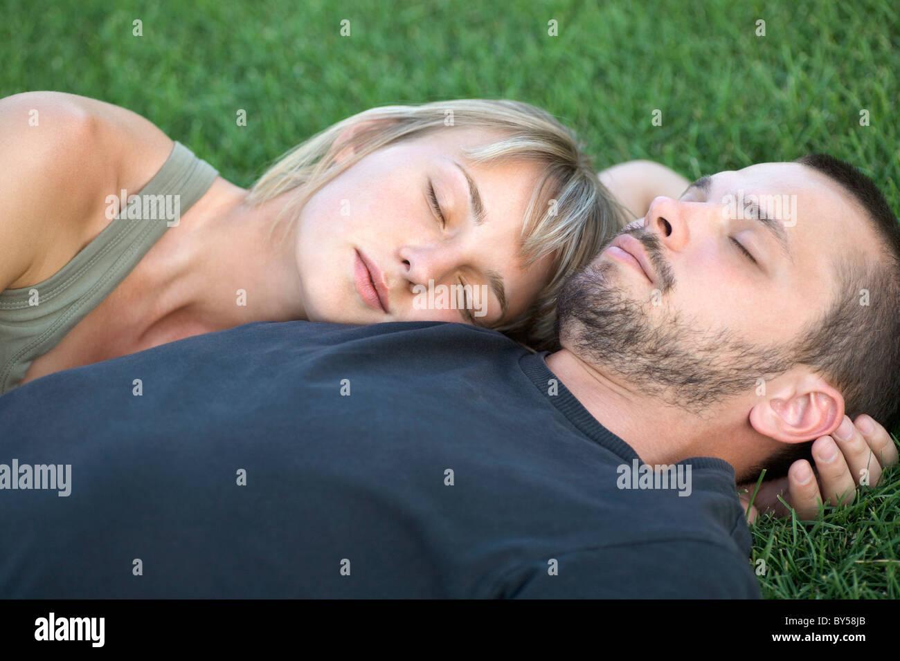 Man and woman sleeping on grass - Stock Image
