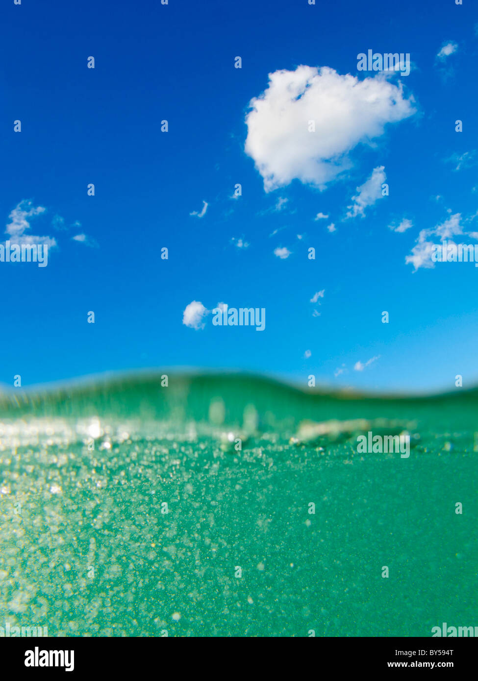 View of the sea with green water and blue skies - Stock Image