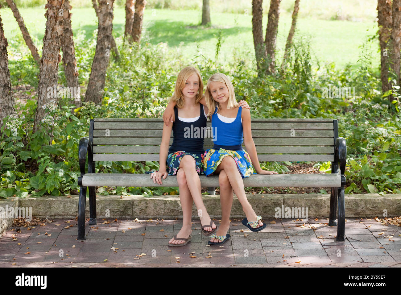 Two Girls legs crossed on a bench Stock Photo