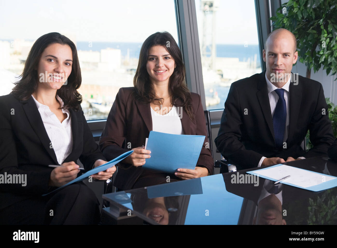 Businessteam of three persons relaxed at the table - Stock Image