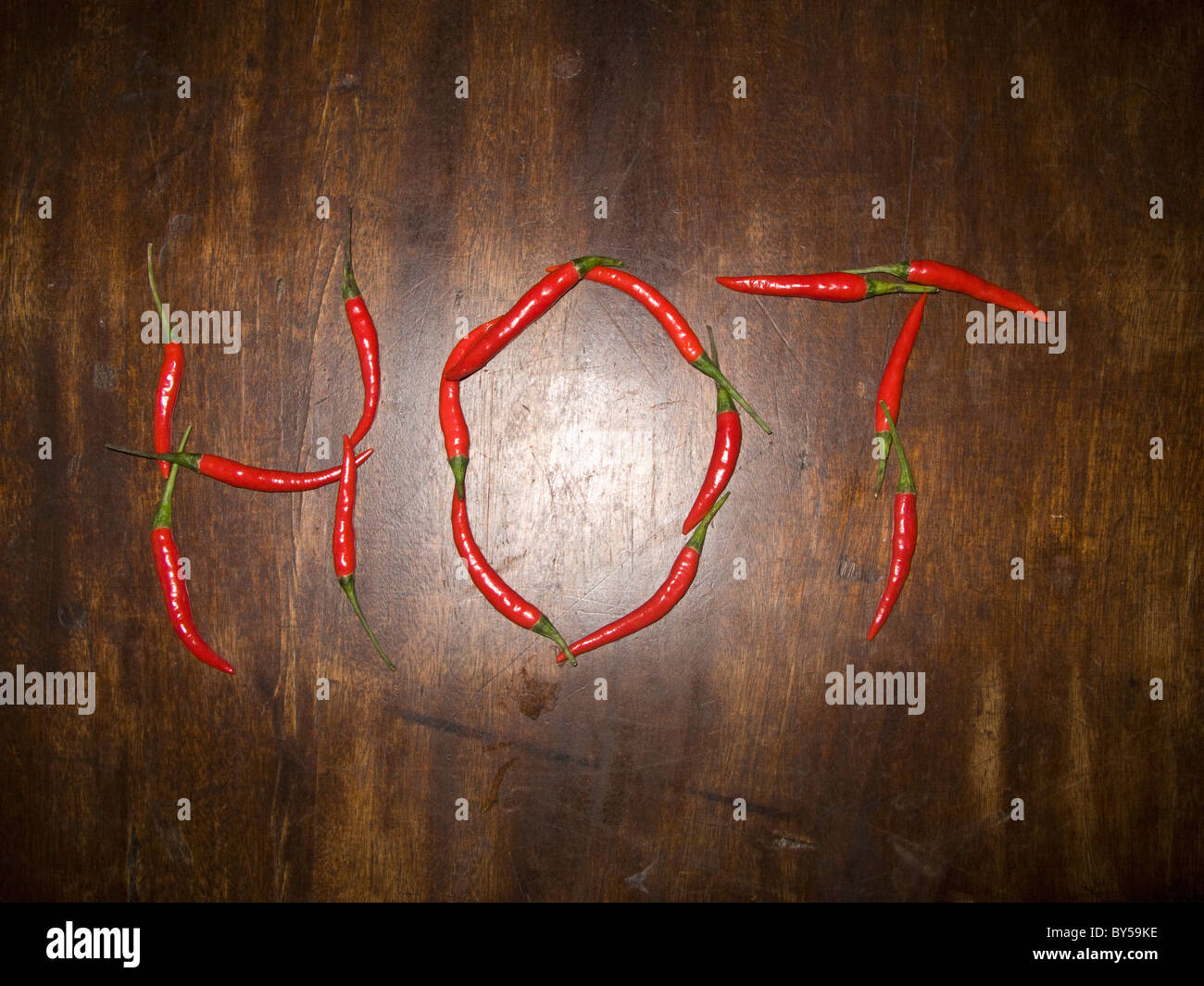 Red chili peppers spelling the word HOT - Stock Image