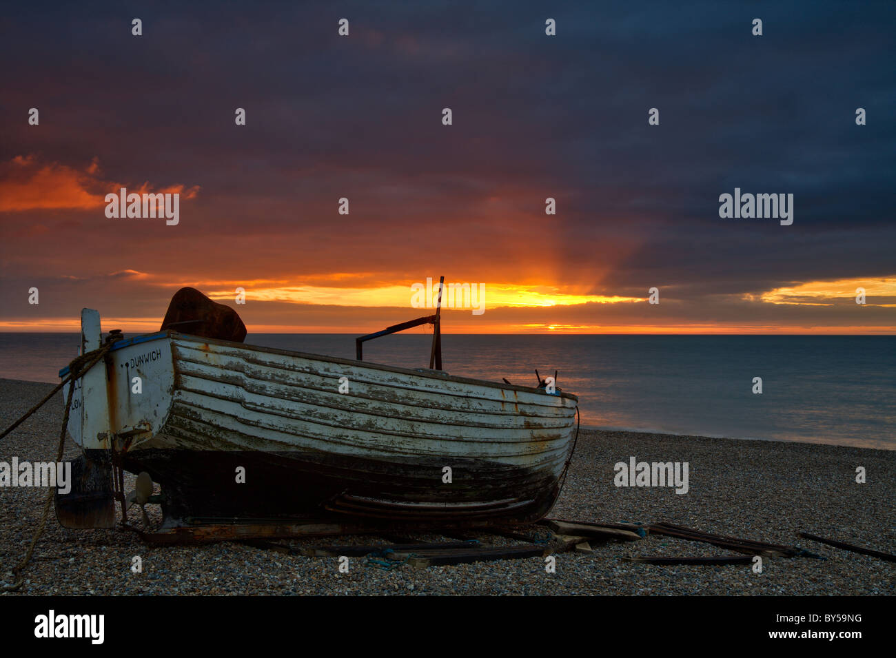 Sunrise Dunwich Beach and traditional Suffolk Fishing boat on shore - Stock Image