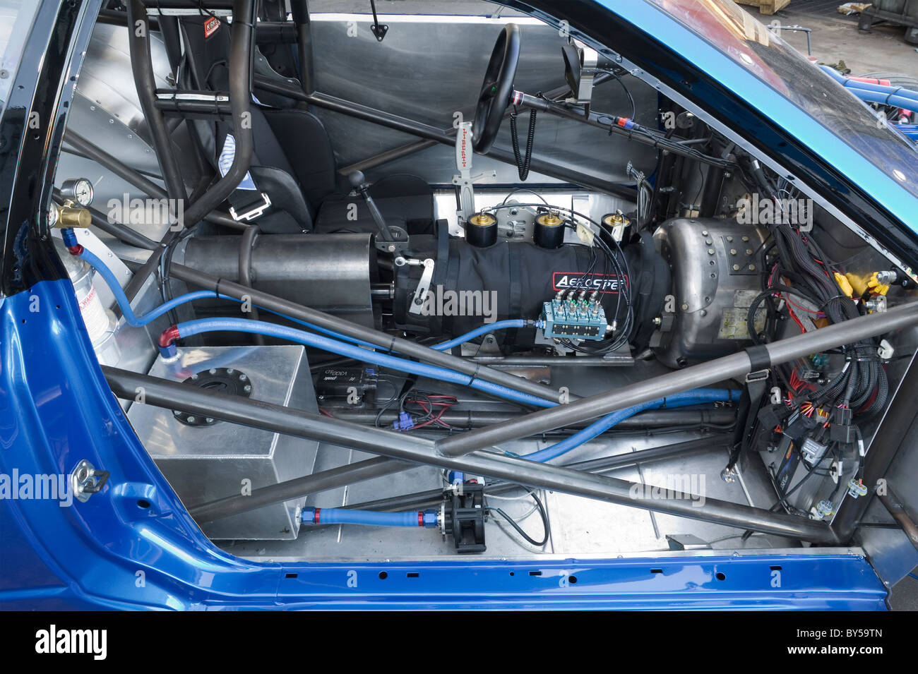 cockpit in a drag racing car showing components and parts such as gearbox,  safety cage, gear shifter, electrical parts etc