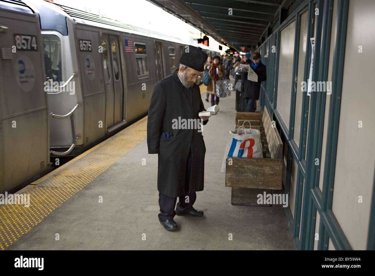 Orthodox Jewish man says prayers on the subway platform as the train enters the station in Williamsburg, Brooklyn, - Stock Image