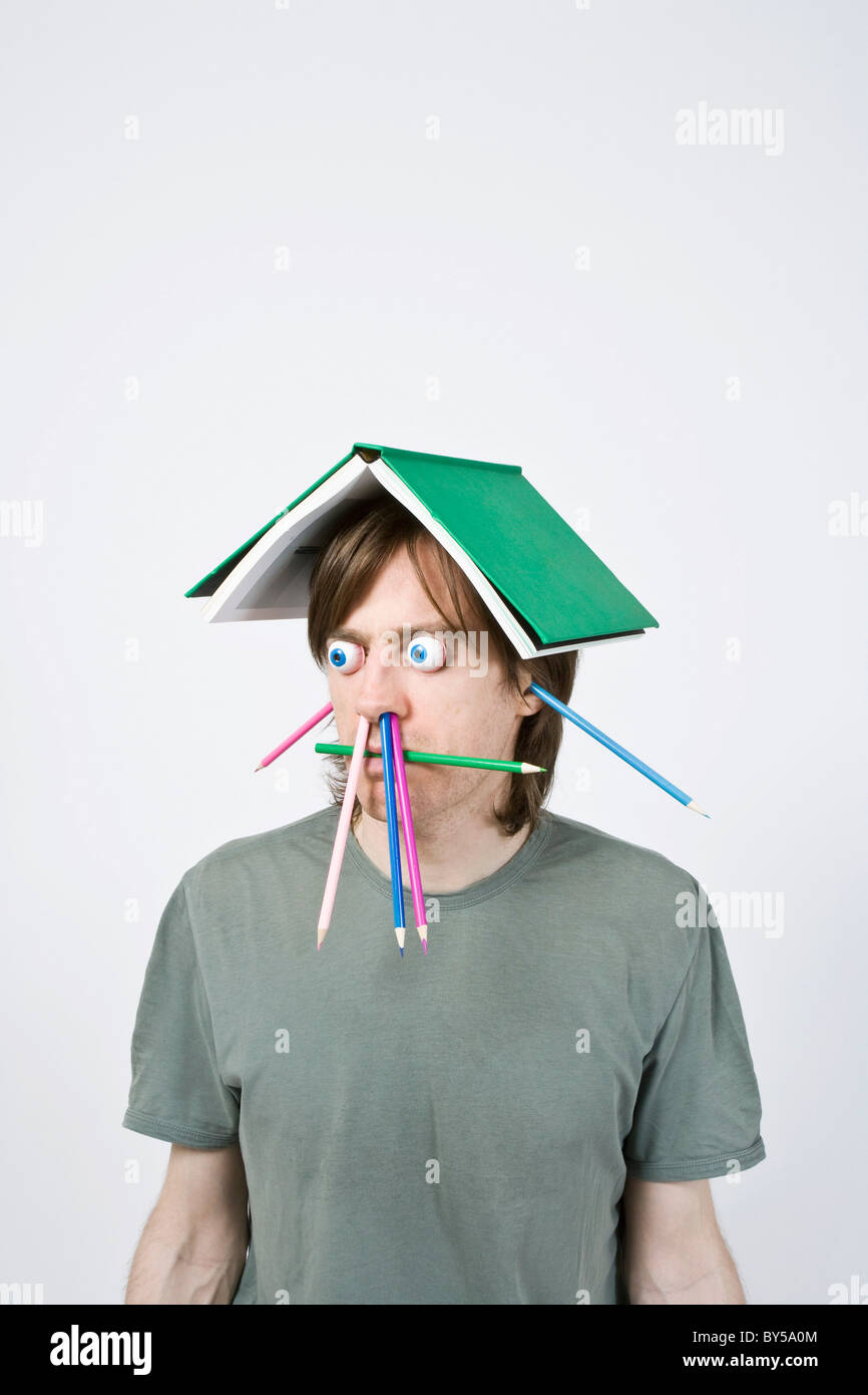 Bizarre man balancing book on head - Stock Image