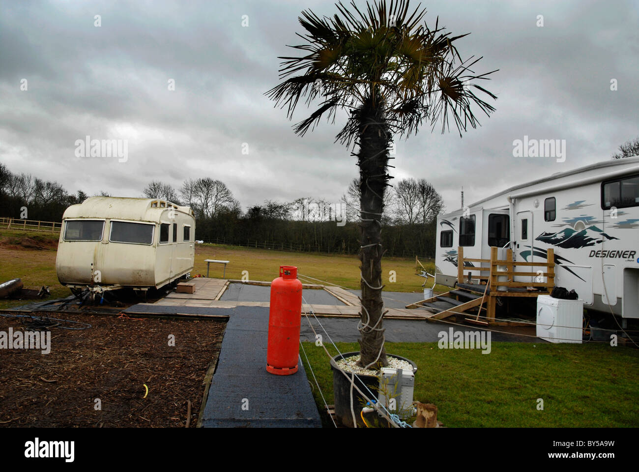 Traveller caravan and potted palm tree in a traveller site at Meriden UK. - Stock Image