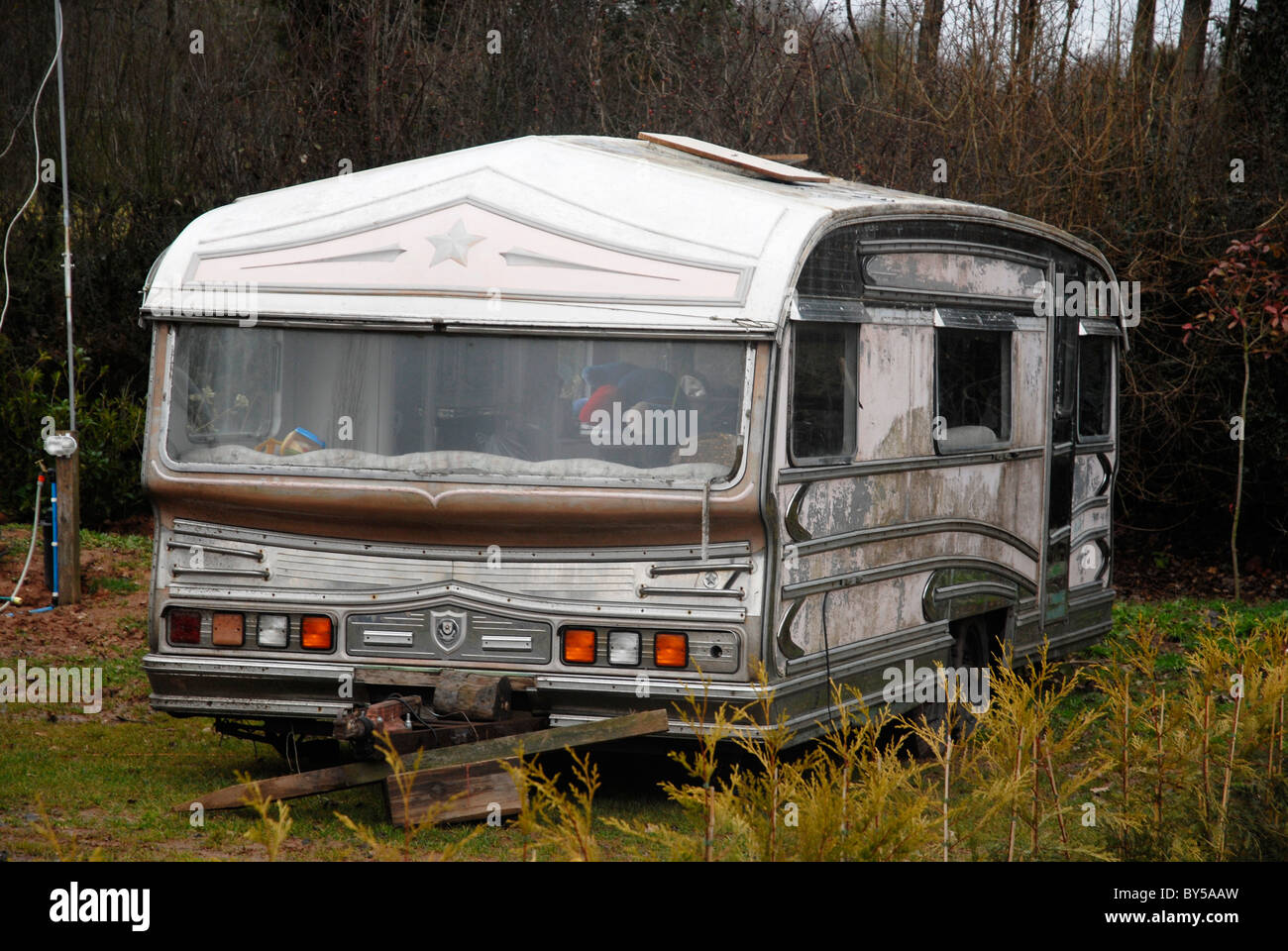 Traveller caravan awaiting restoration in a traveller site at Meriden UK. - Stock Image