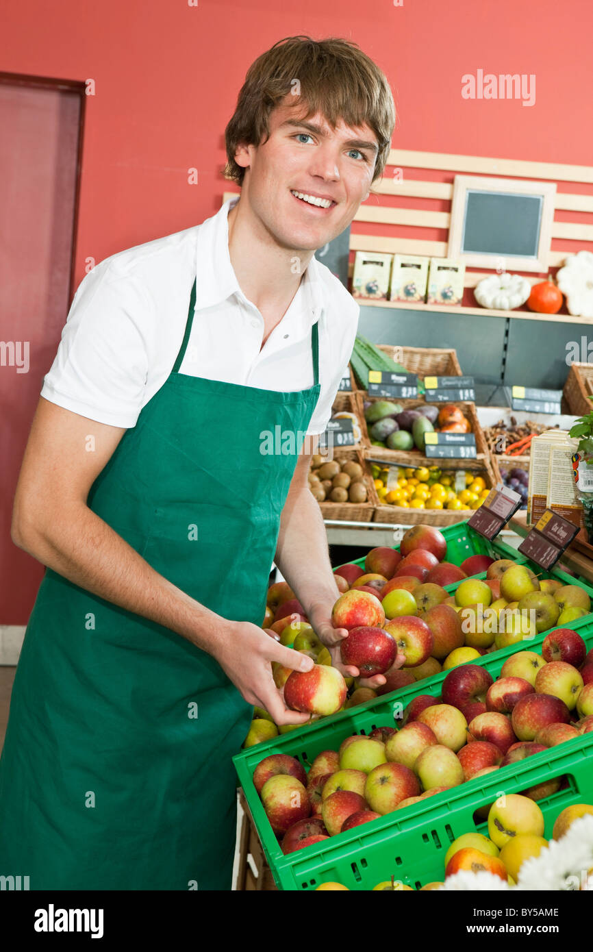 A grocery stocker stocking apples - Stock Image