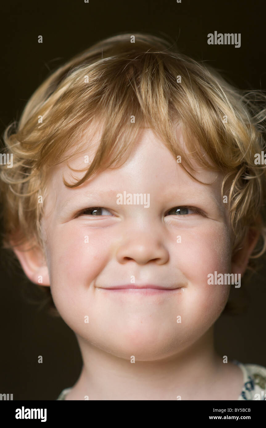 Portrait of a two year old capturing his cheeky grin - Stock Image
