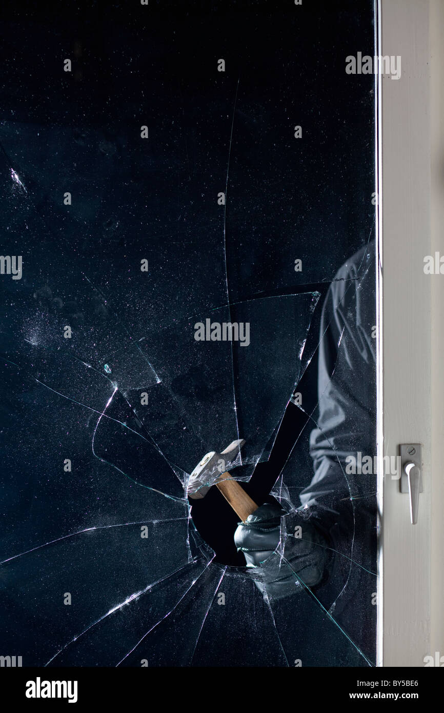 A criminal breaking into a window, focus on hand - Stock Image