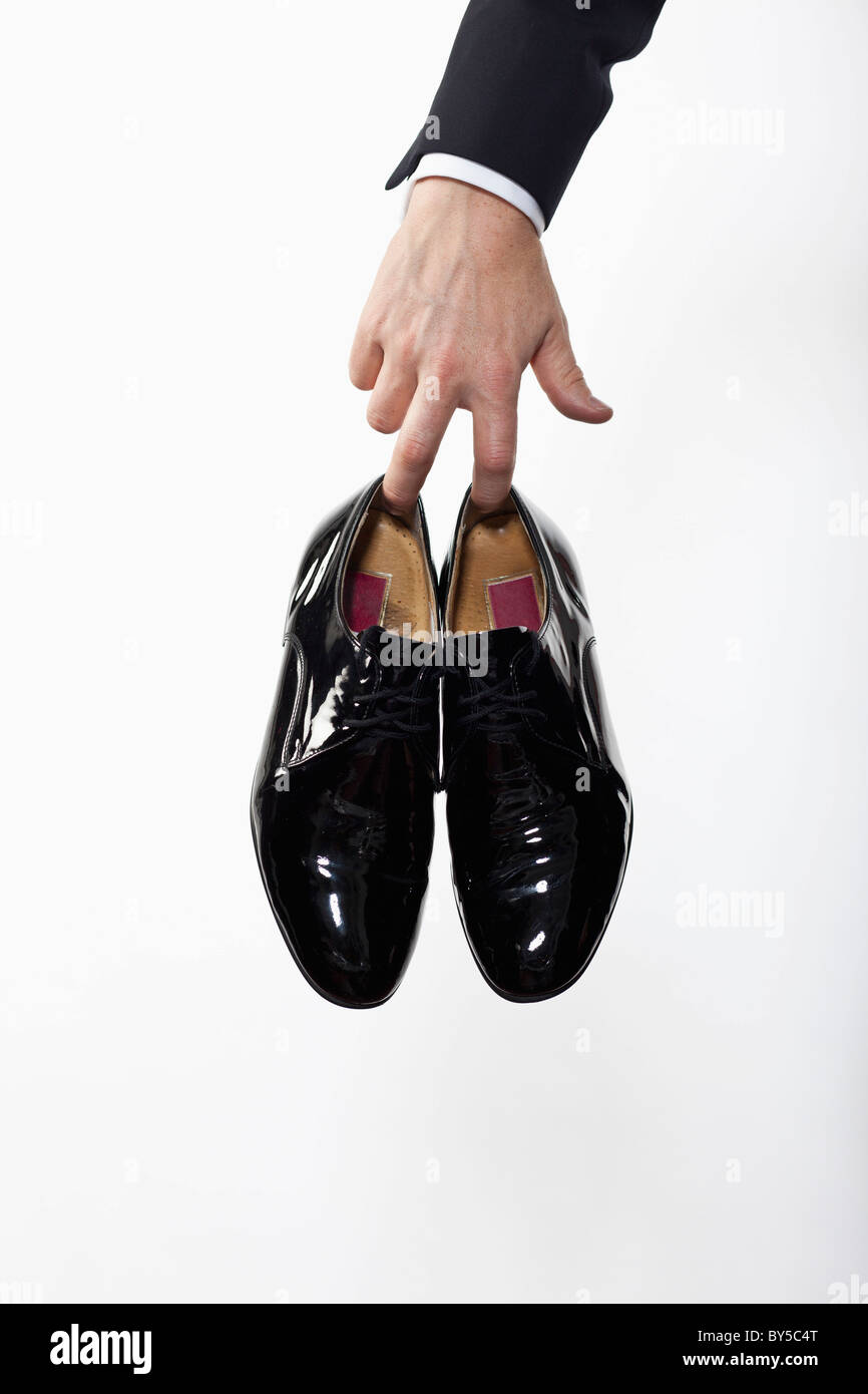 6a9e4e21 A man holding a pair of patent leather dress shoes, focus on hand ...