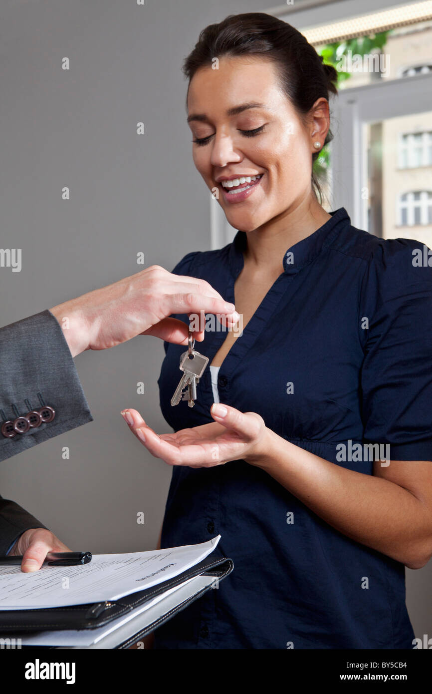 A real estate agent giving a woman the keys to her new home Stock Photo