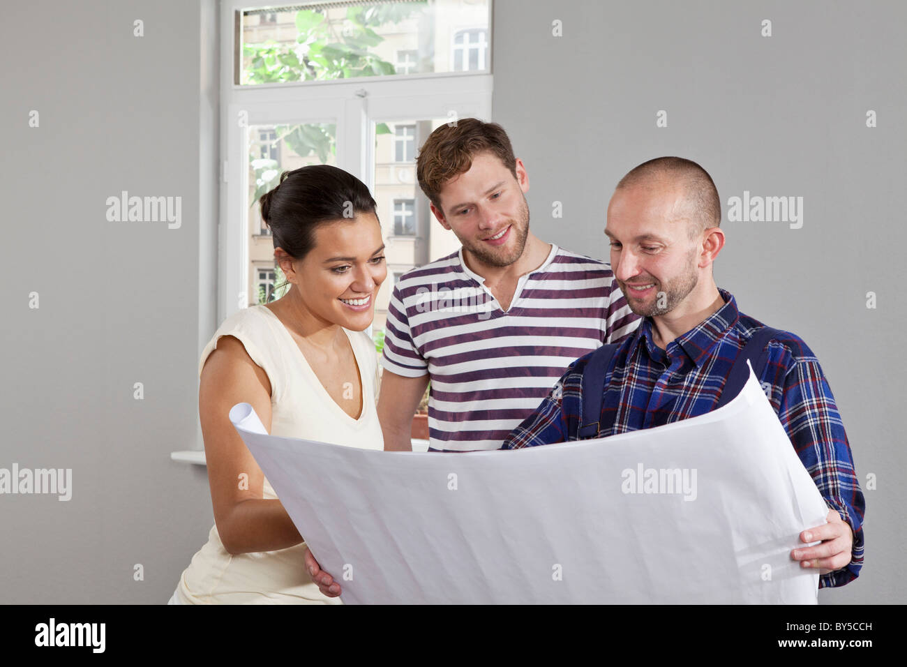 A building contractor showing blueprints to a young couple - Stock Image