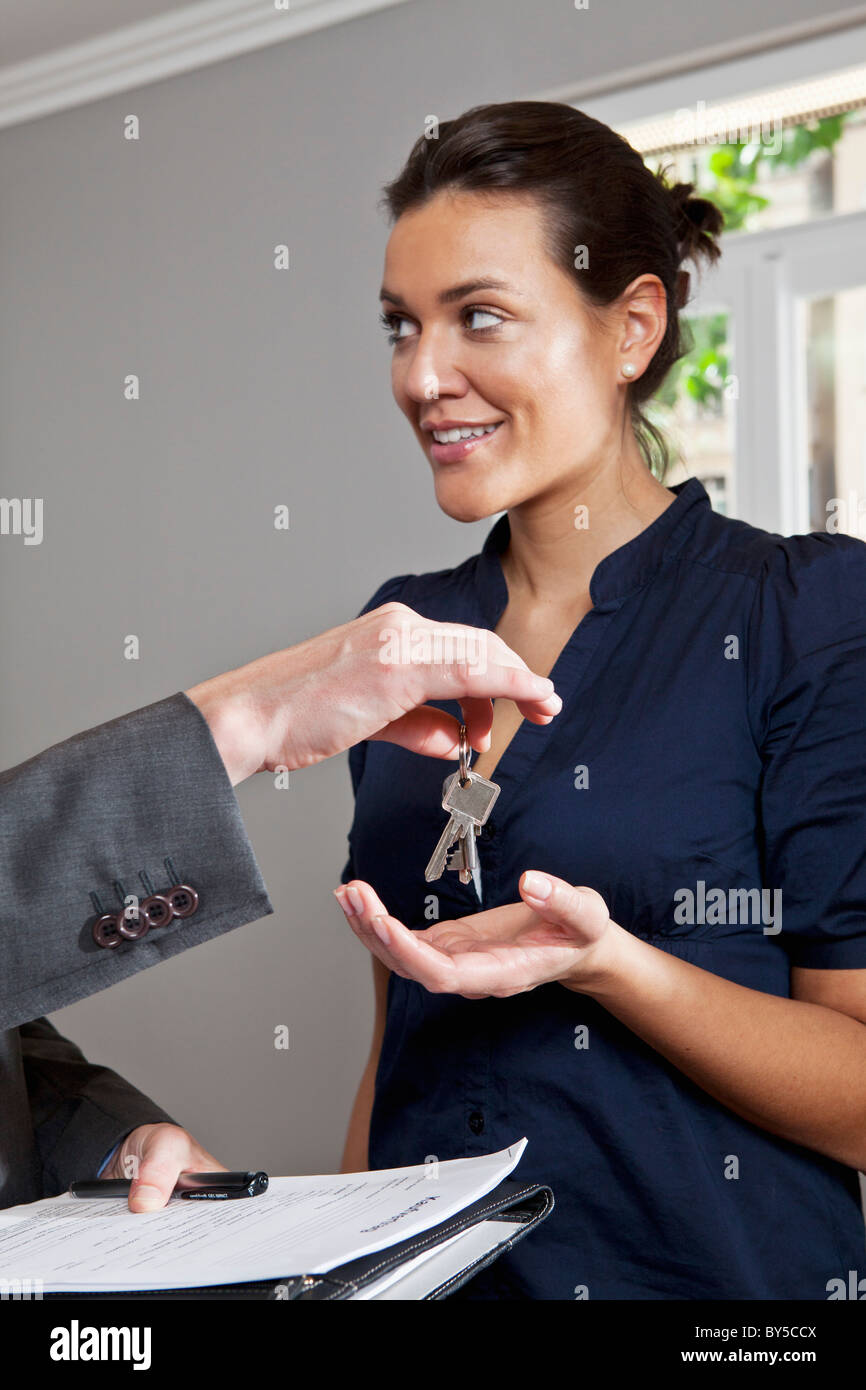A real estate agent giving a woman the keys to her new home - Stock Image