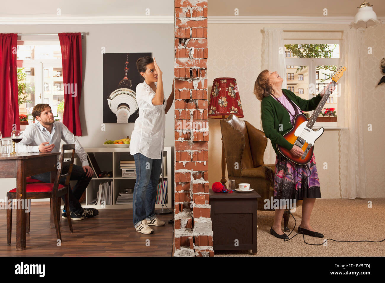 A split screen showing an angry woman pounding on the wall to her neighbor - Stock Image