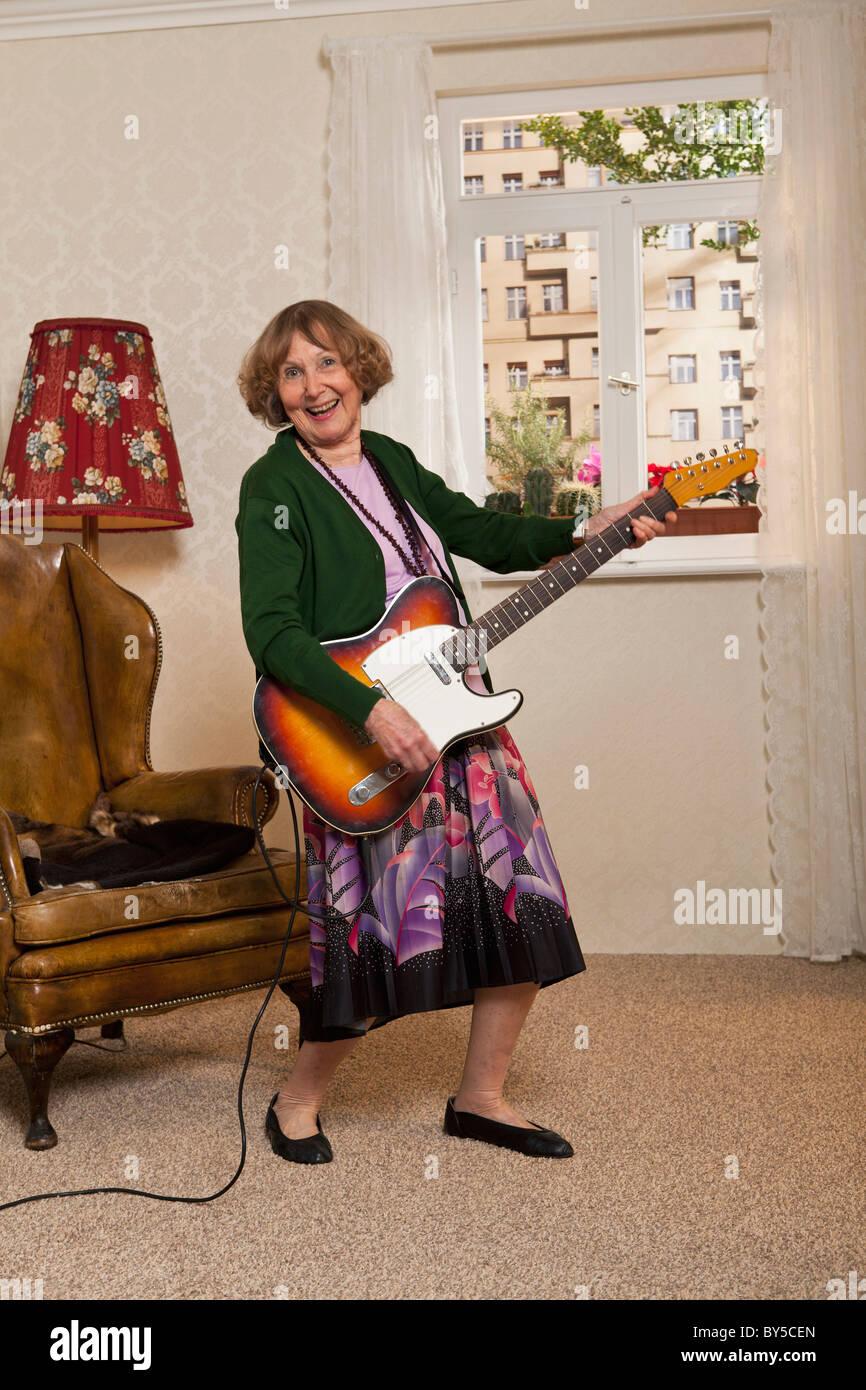 A senior woman playing an electric guitar - Stock Image