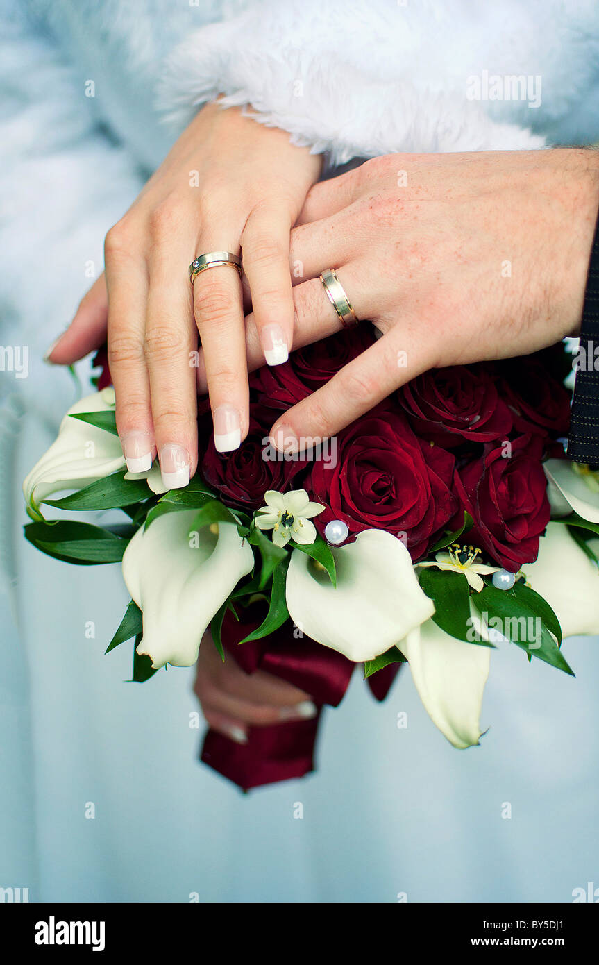 Hands with wedding gold rings and flowers - Stock Image