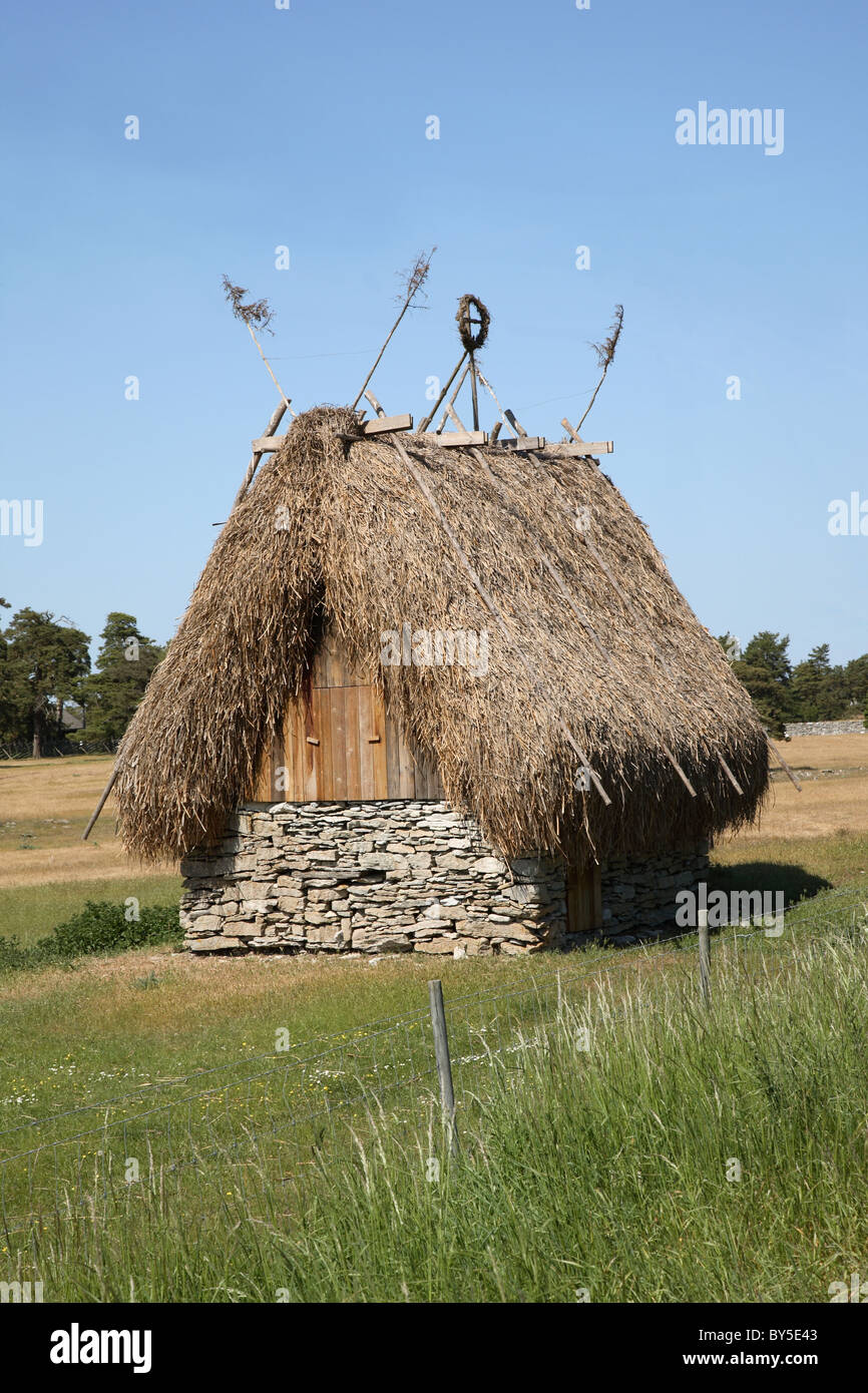 Old farm building in local style with thatched roof on the Swedish island Fårö close to Gotland in the Baltic Sea. Stock Photo