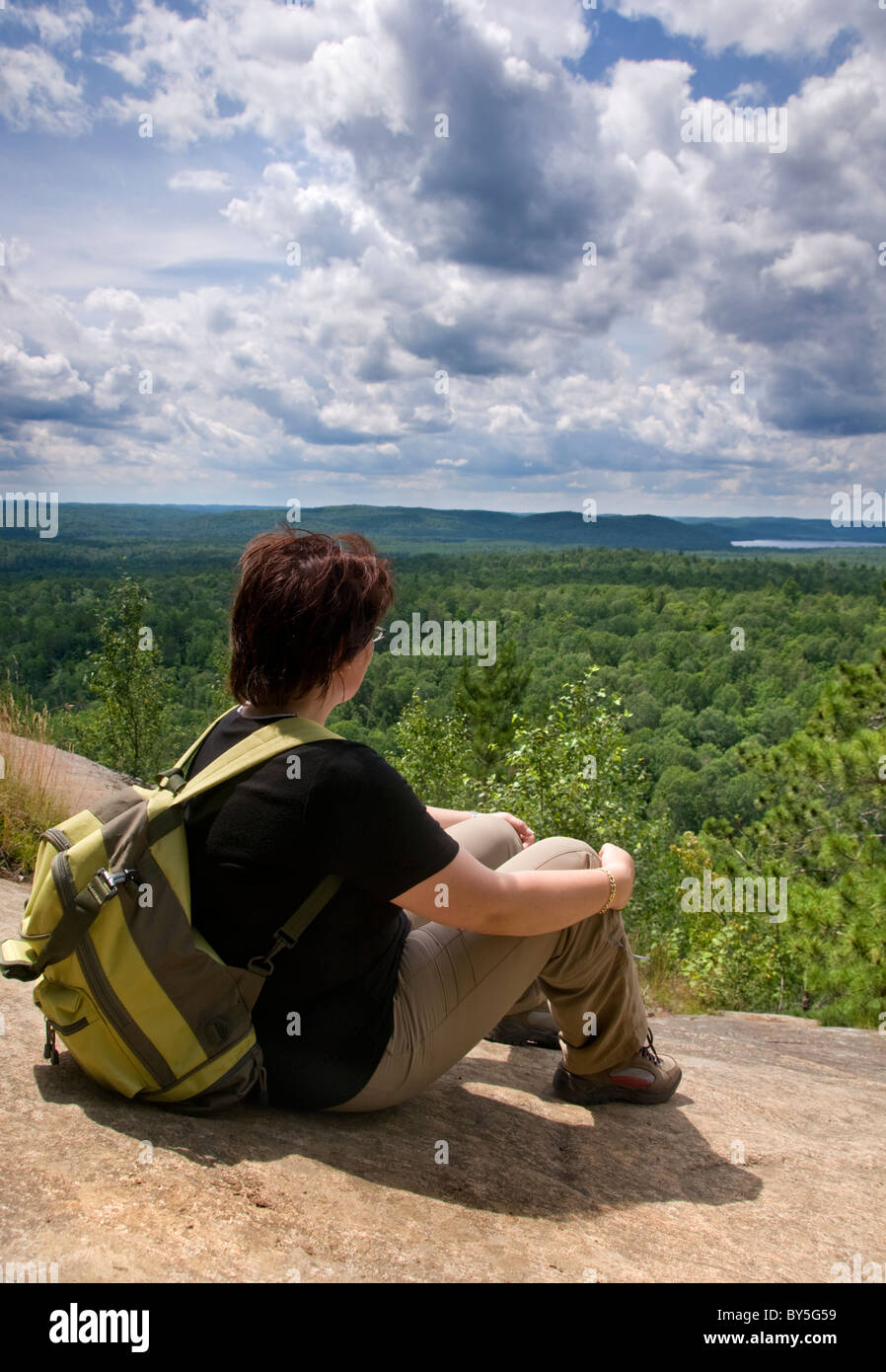 A female hiker looking out over Algonquin Provincial Park in Ontario, Canada, from a high vantage point on the Lookout - Stock Image