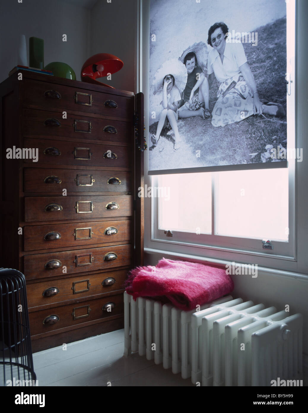 Black+white photograph-patterned blind on window above large radiator in study with tall antique chest-of-drawers - Stock Image