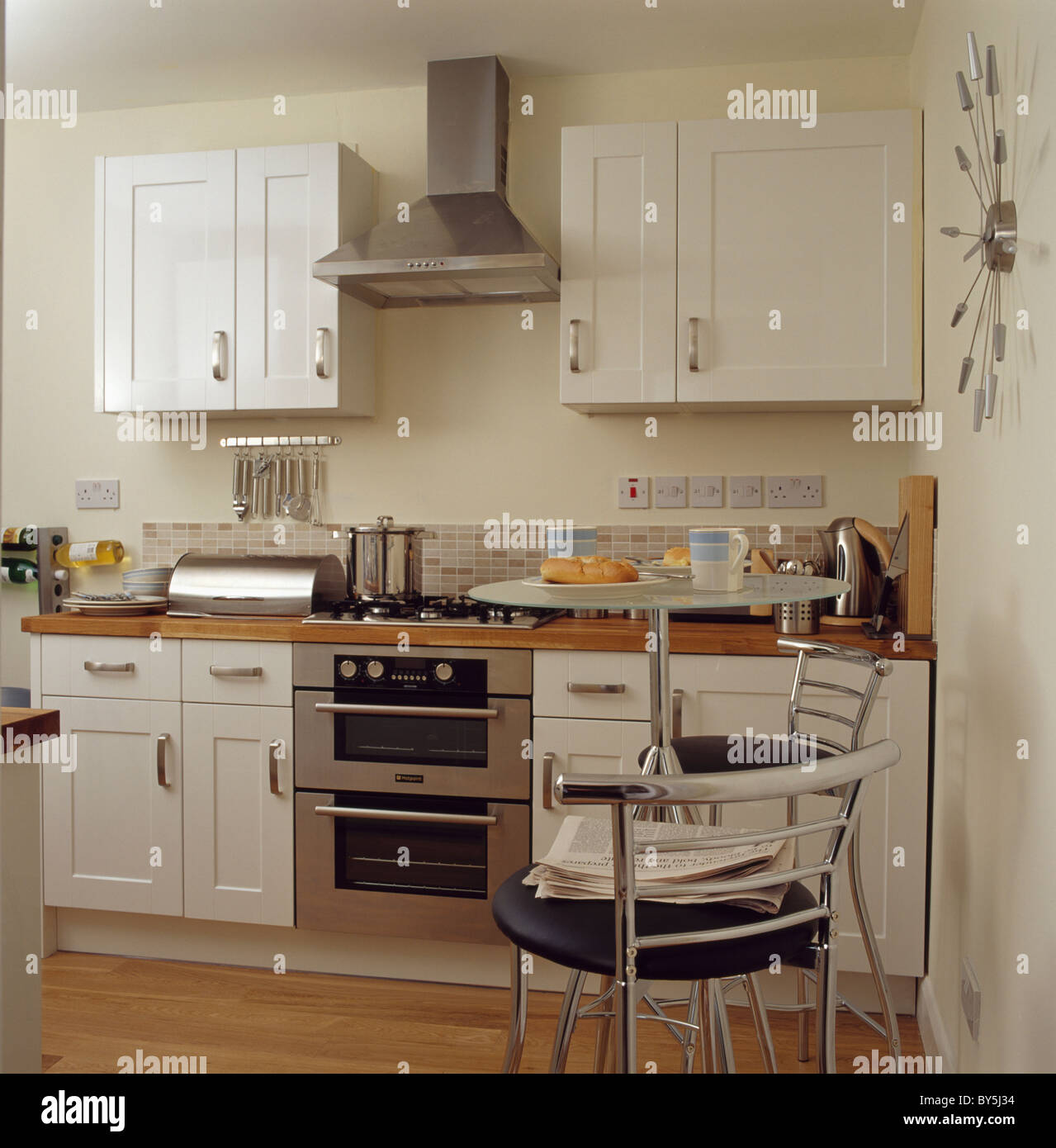 Off White Kitchen Cabinets With Stainless Appliances: Stainless Steel Extractor Above Steel Oven In Modern Cream