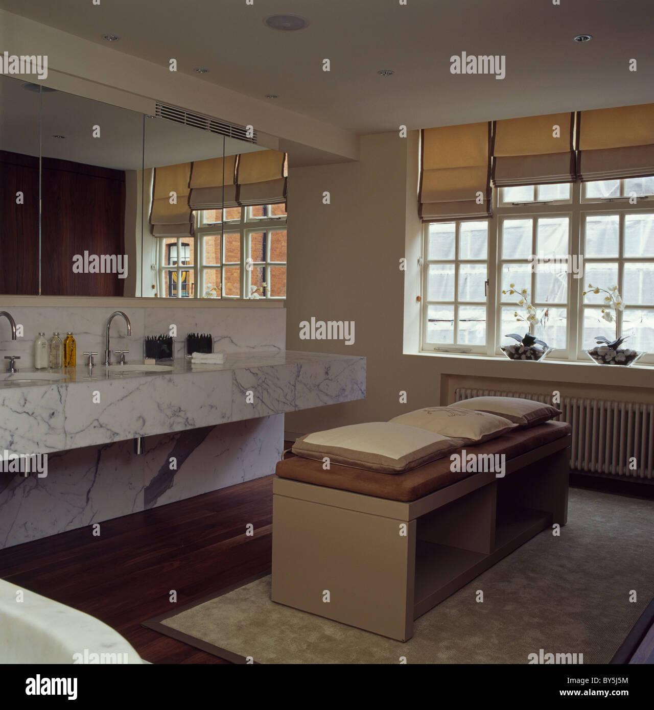 Large mirror above double basins in marble vanity unit in modern en-suite bathroom - Stock Image