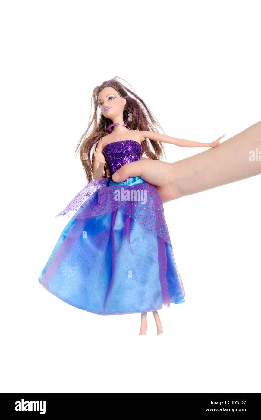 Child holding a barbie doll in her hand - Stock Image