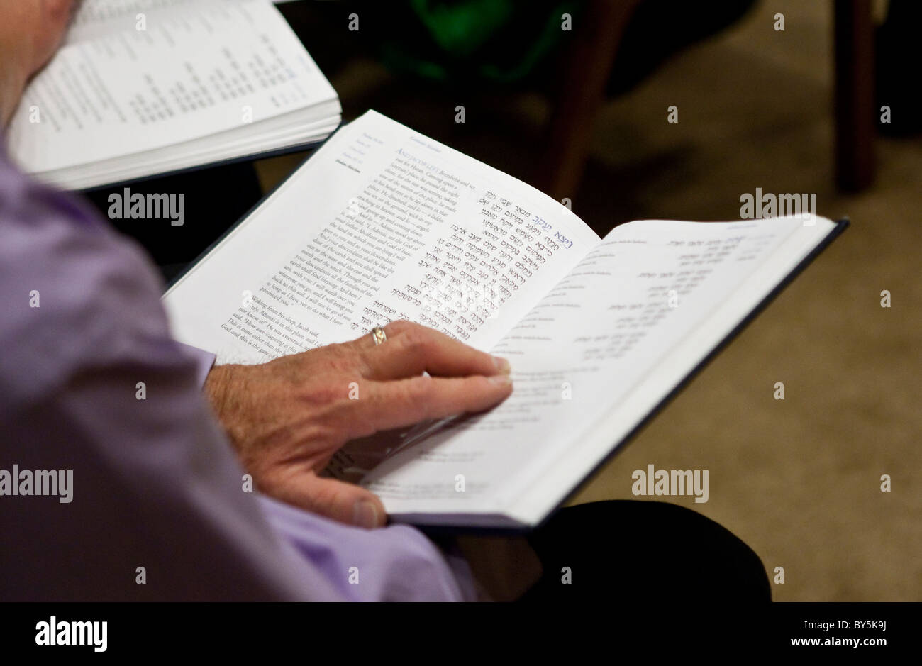 Congregation member reads from Hebrew-English prayer book during Sabbath service at Reform Jewish synagogue in Austin, - Stock Image