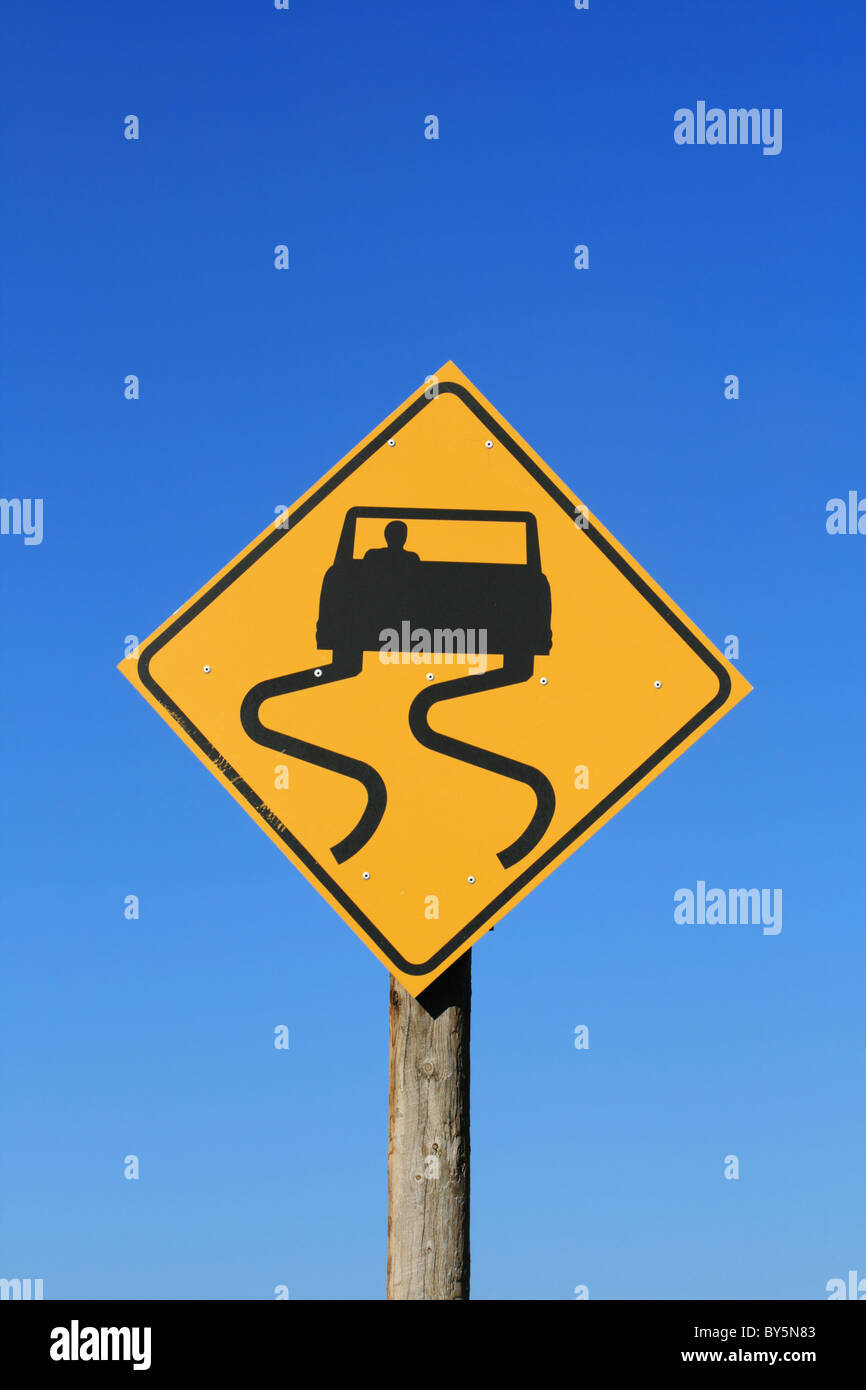 slippery road sign with car and skid marks in black on yellow with blue sky background - Stock Image