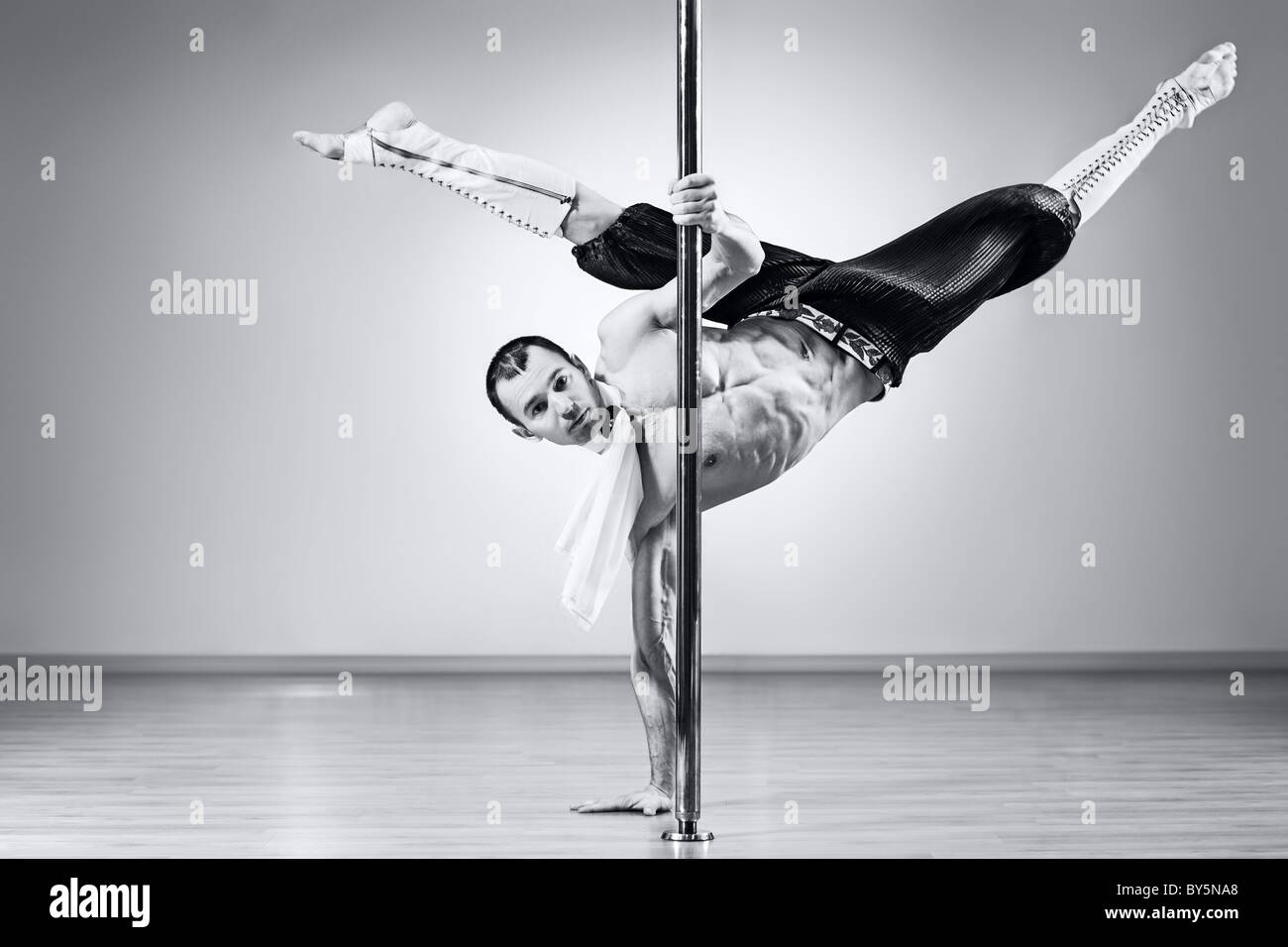 Young strong pole dance man. Black and white colors. - Stock Image