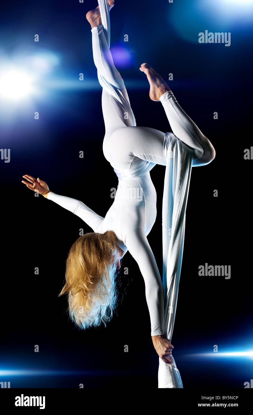 Young woman gymnast. On black background with flashes effect. - Stock Image