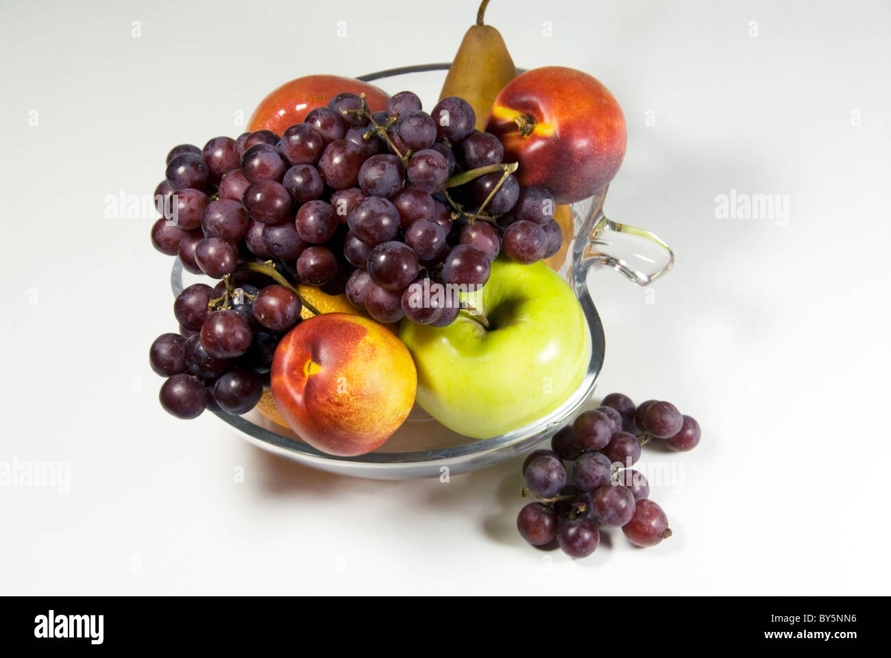 Stock photo of fruit bowl filled with grapes, apples, oranges and a pear. The bowl is apple shaped. - Stock Image