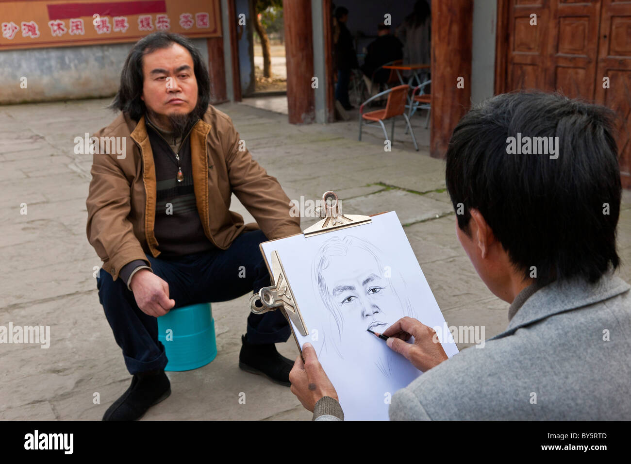 Street artist making a pencil sketch of a man in Huanglongxi, near Chengdu, Sichuan Province, China. JMH4349 - Stock Image
