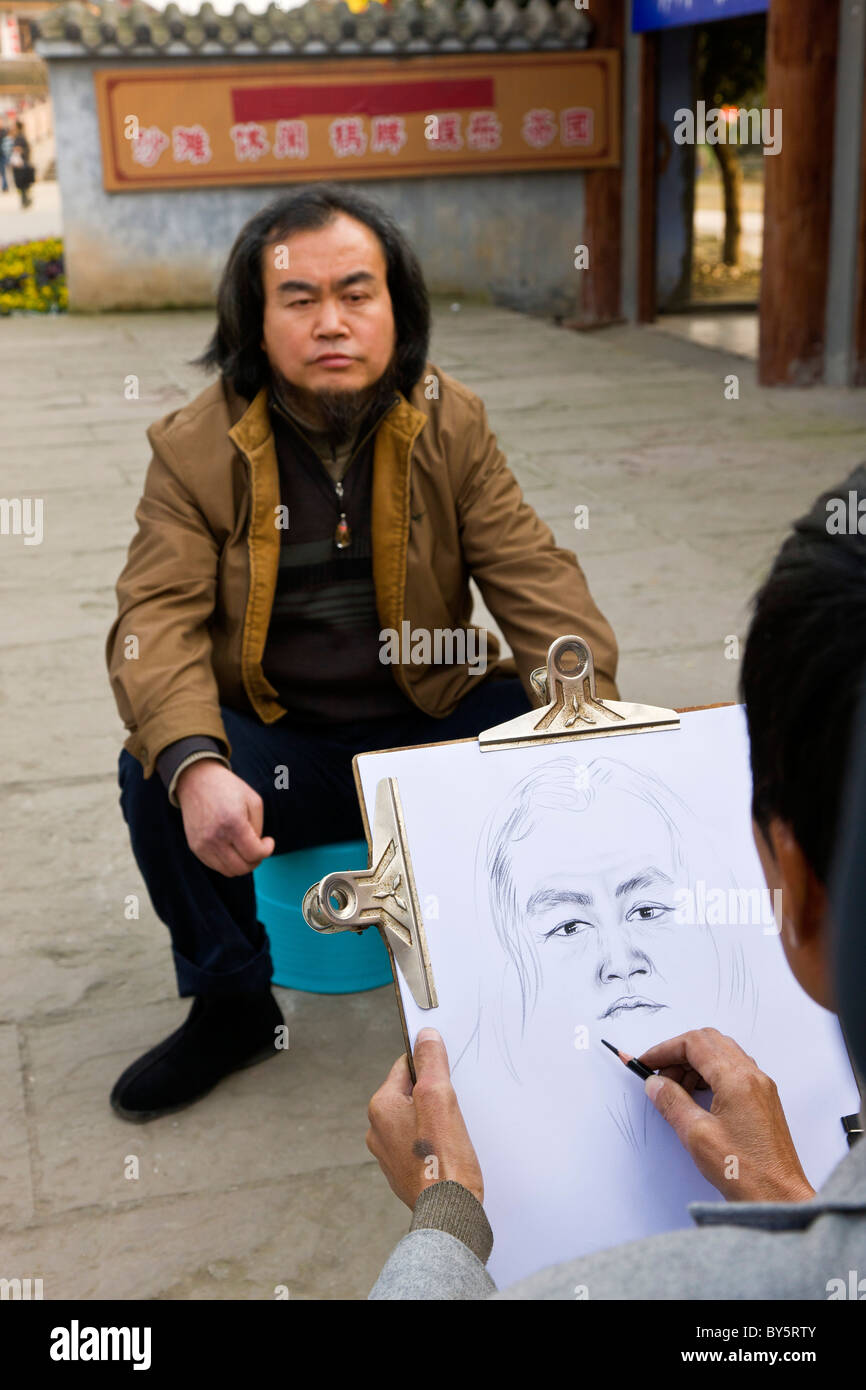 Street artist making a pencil sketch of a man in Huanglongxi, near Chengdu, Sichuan Province, China. JMH4350 - Stock Image