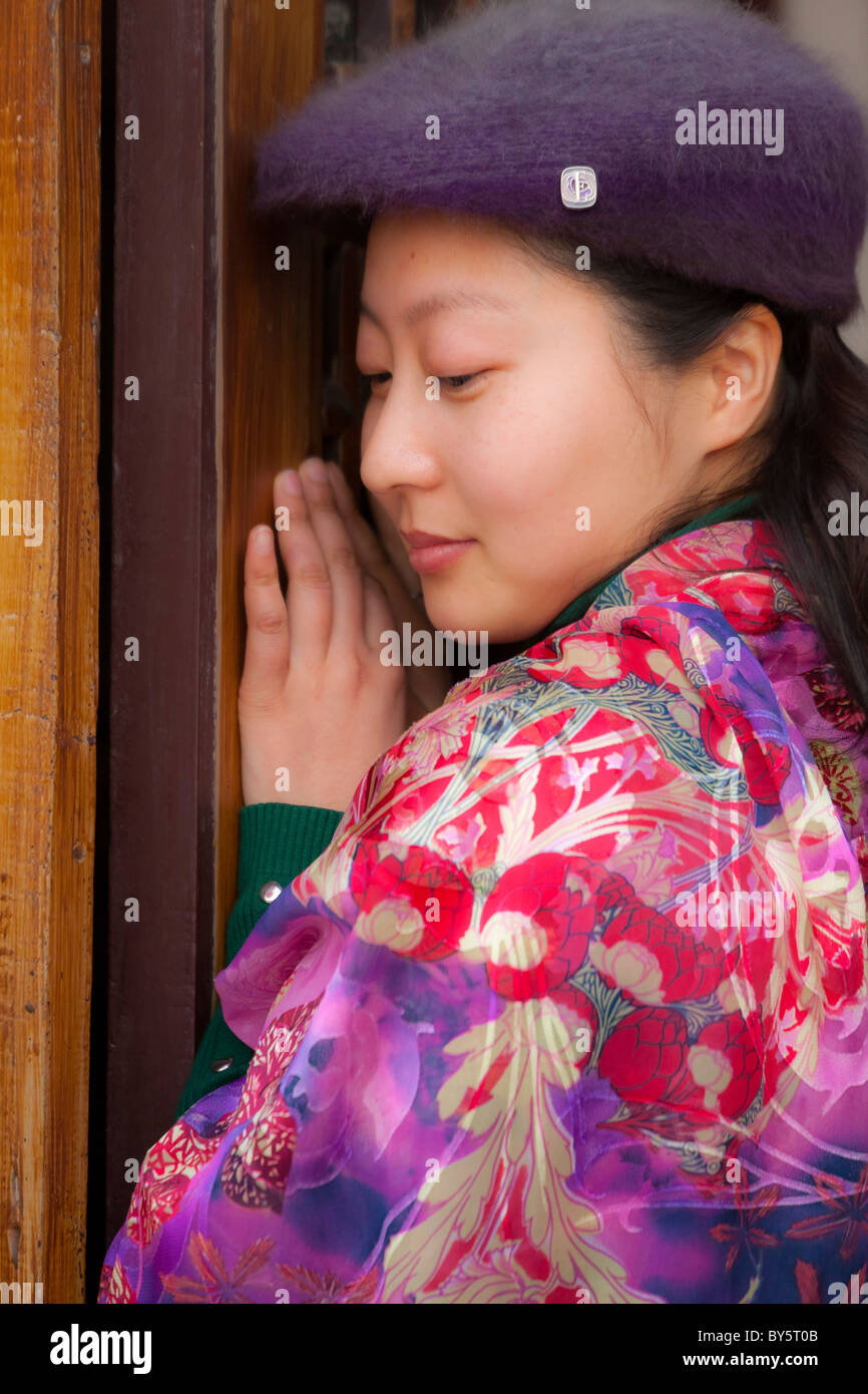 9835a9f4c5a Beautiful shy young Chinese girl wearing colourful floral silk pashmina and  purple cap in Huanglongxi