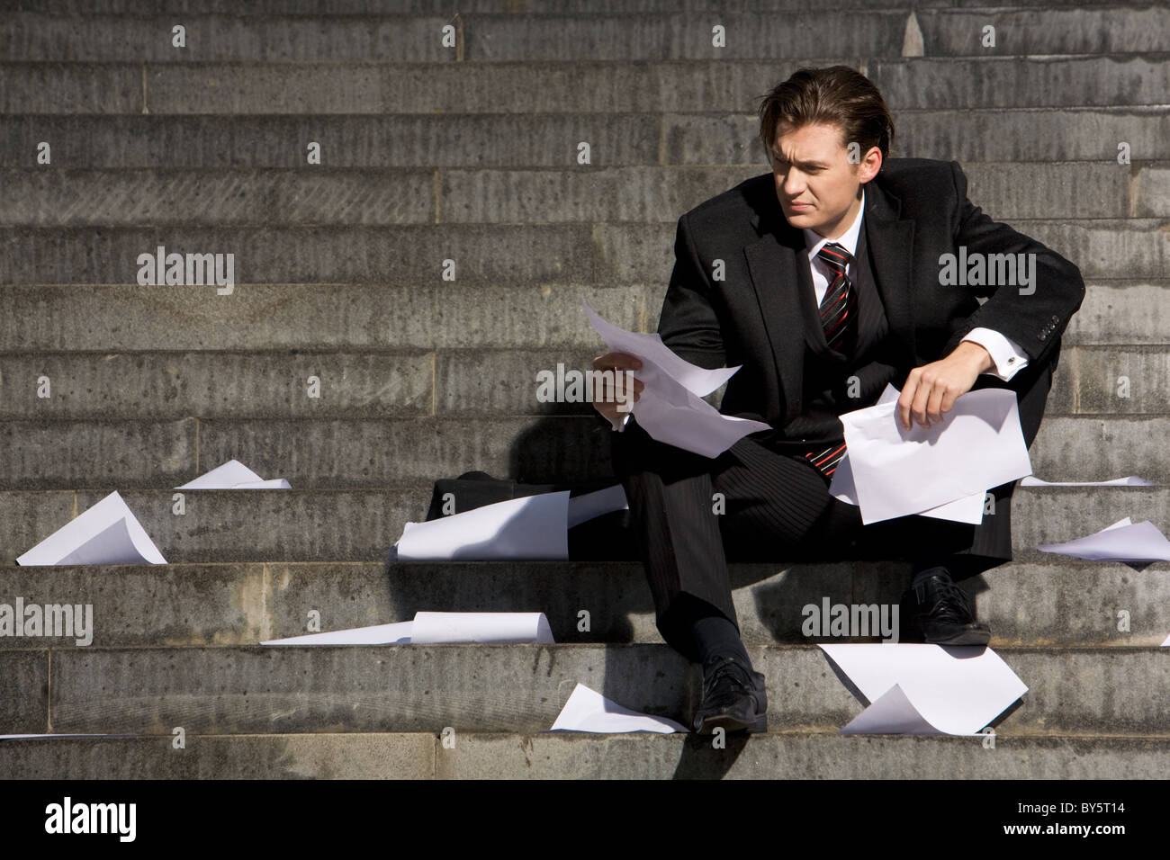 Unhappy businessman suffering from world financial crisis while sitting on stairs - Stock Image