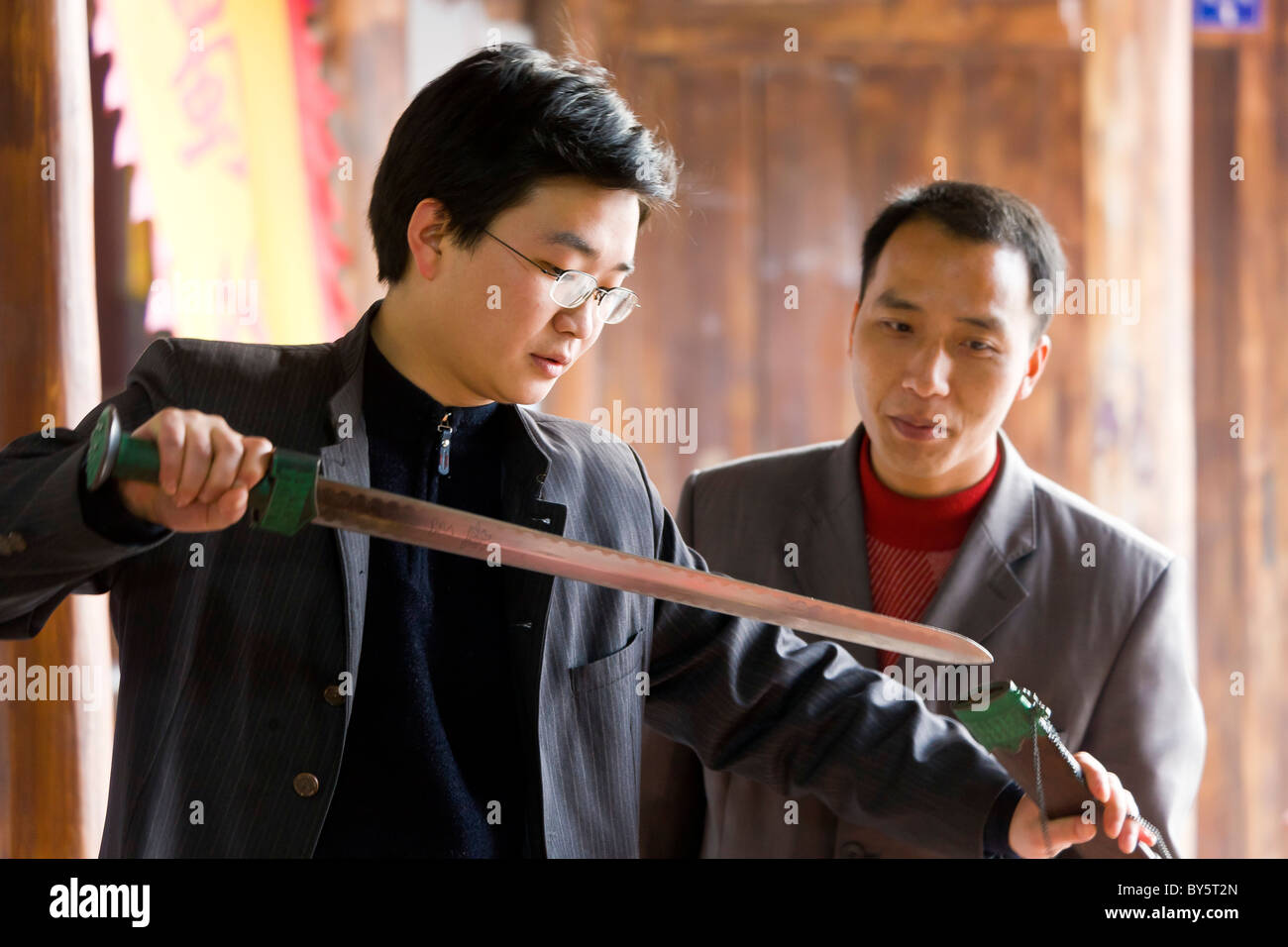 Two men inspect sword in antique shop in Huanglongxi, near Chengdu, Sichuan Province, China. JMH4365 - Stock Image