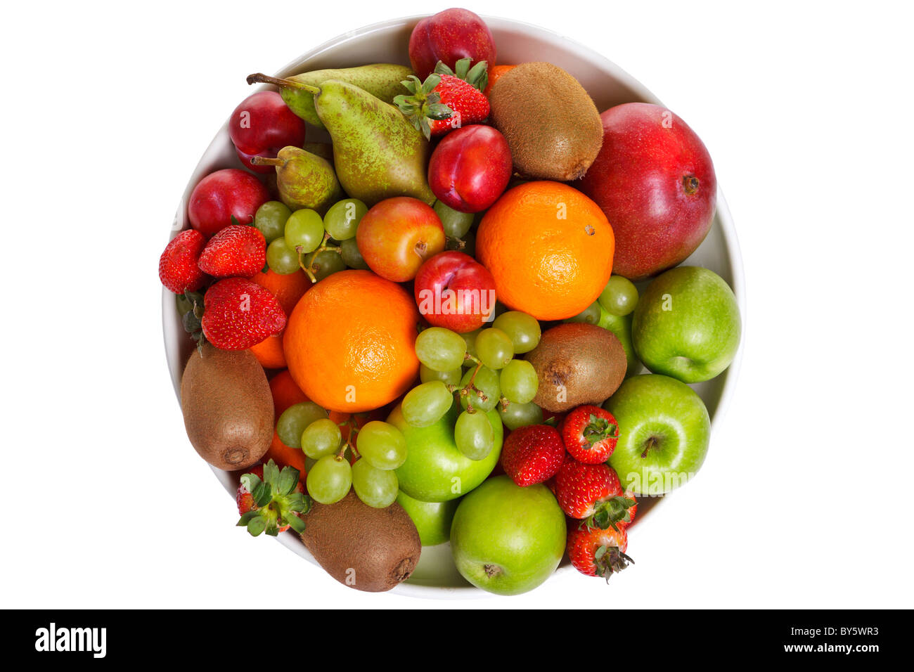 Photo of a bowl of fresh fruit isolated on a white background, shot from above. - Stock Image