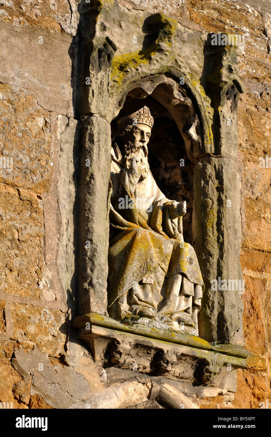 Statue of St. Wilfrid over south porch of Kibworth Church, Leicestershire, England, UK - Stock Image