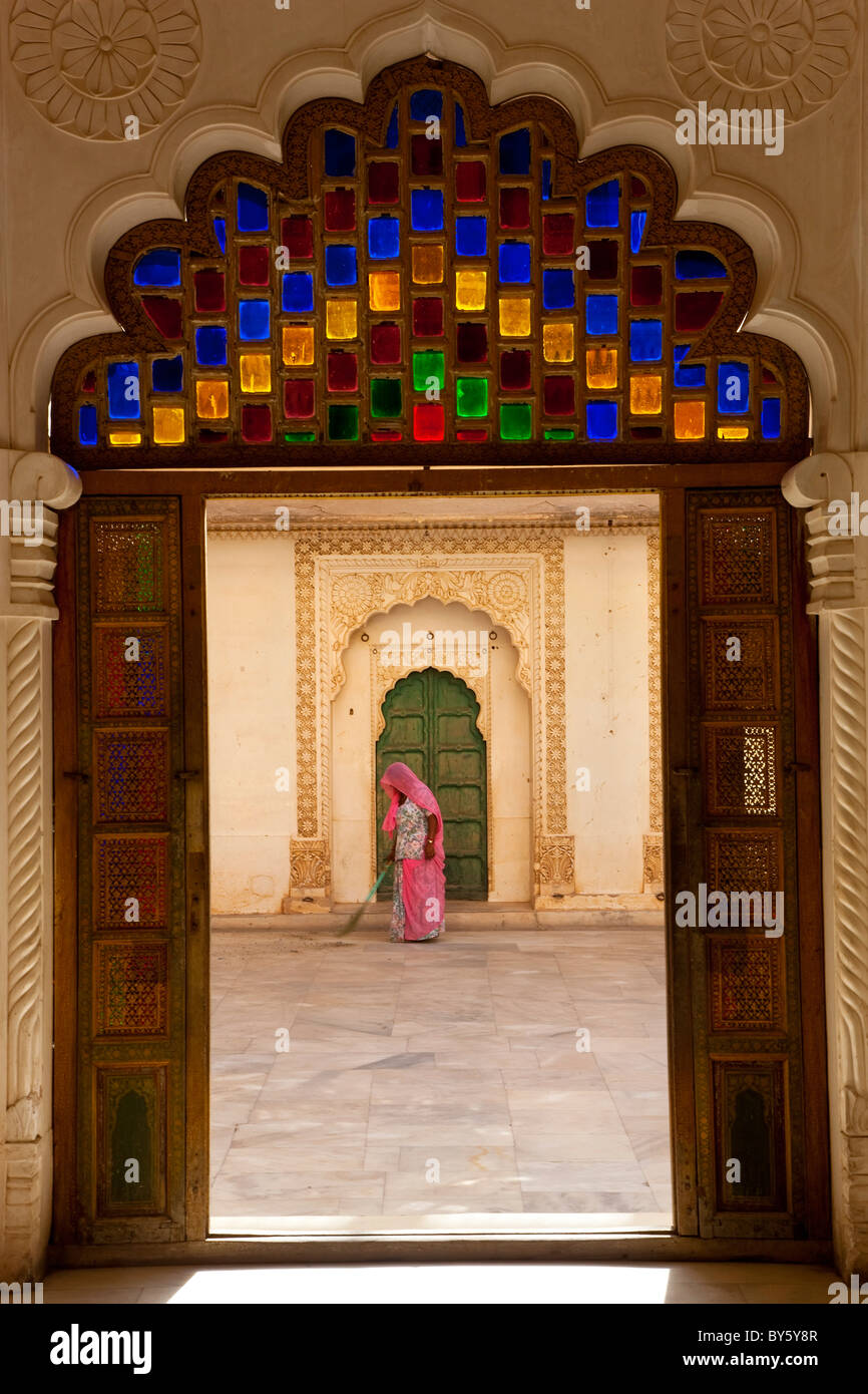 View through doorway of woman sweeping, Meherangarh Fort, Jodhpur, Rajasthan, India - Stock Image
