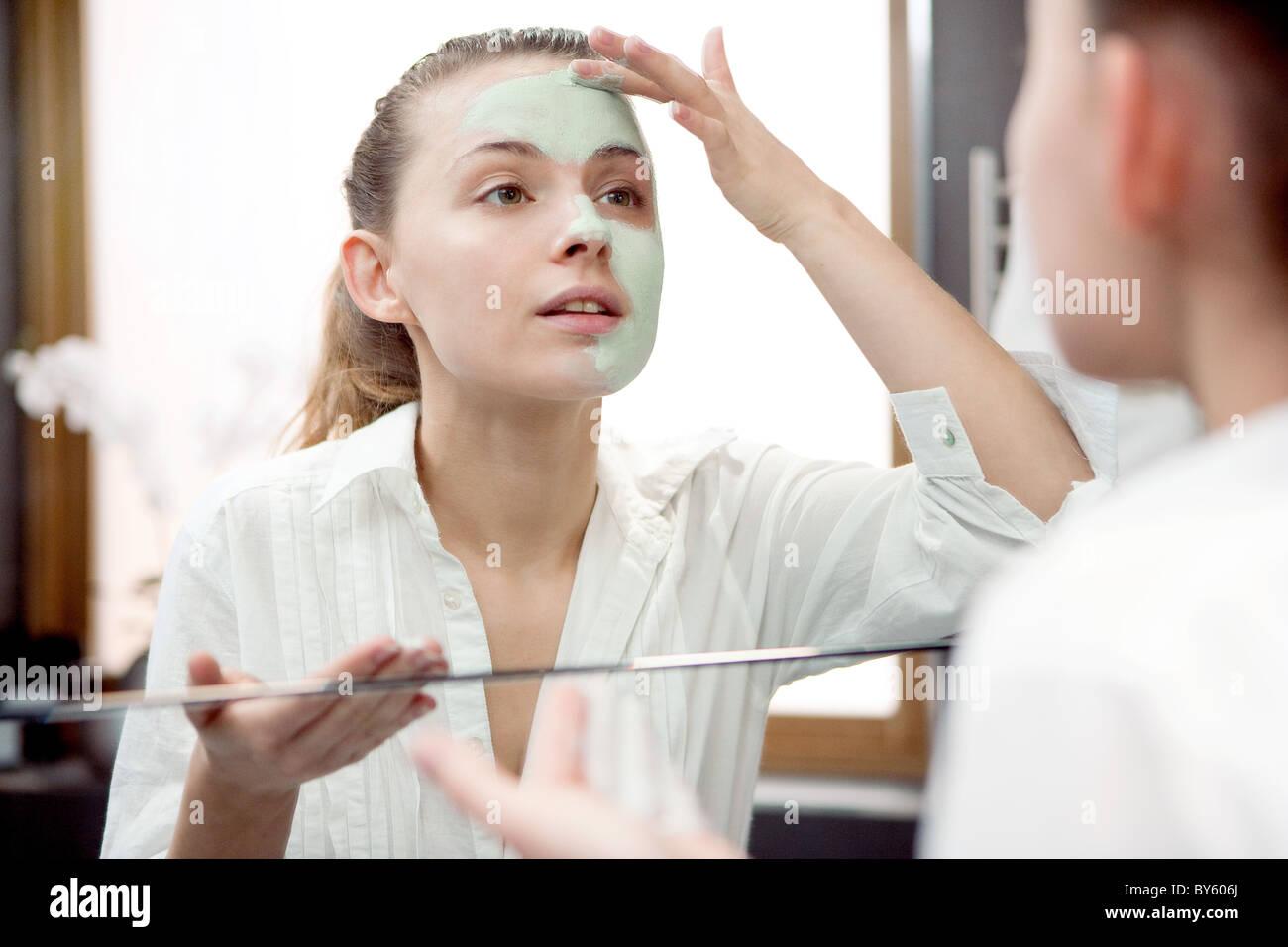 woman applying face mask - Stock Image