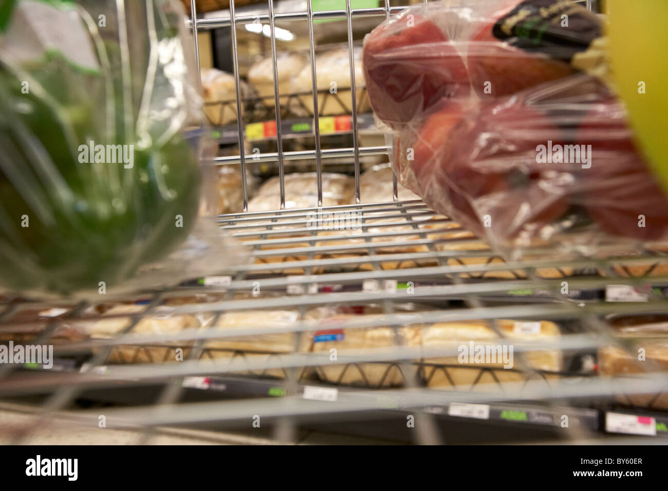 view from a shopping trolley with fruit and veg in the bread aisle in a uk supermarket - Stock Image