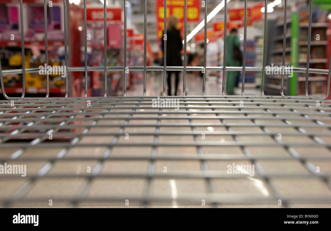 view from an empty shopping trolley in an aisle of a uk supermarket - Stock Image