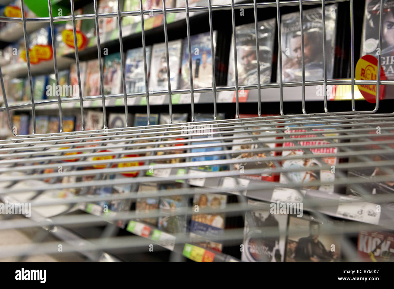 view from an empty shopping trolley in a dvd sales aisle of a uk supermarket - Stock Image