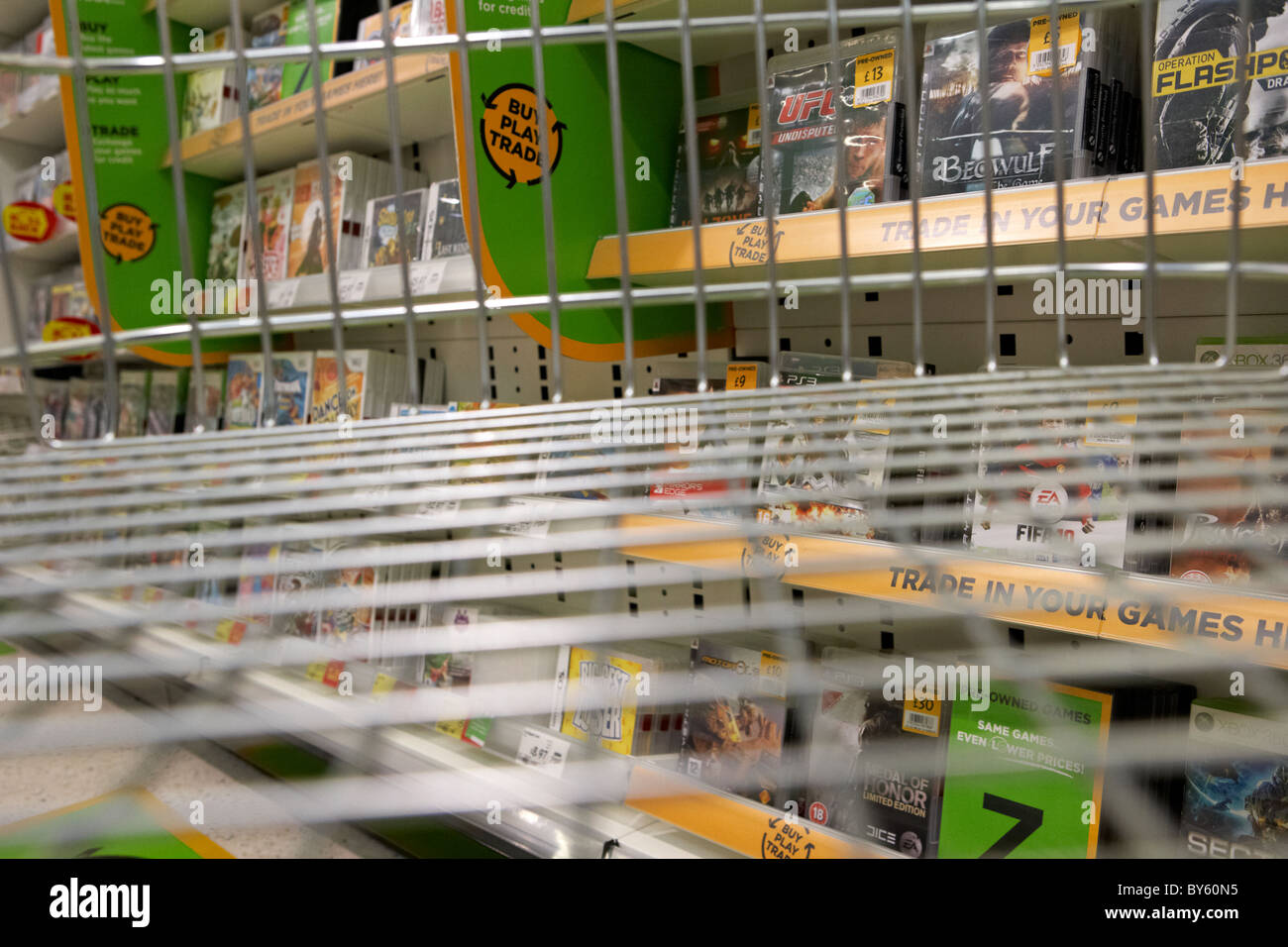 view from an empty shopping trolley in the console games and pre-owned aisle of a uk supermarket - Stock Image