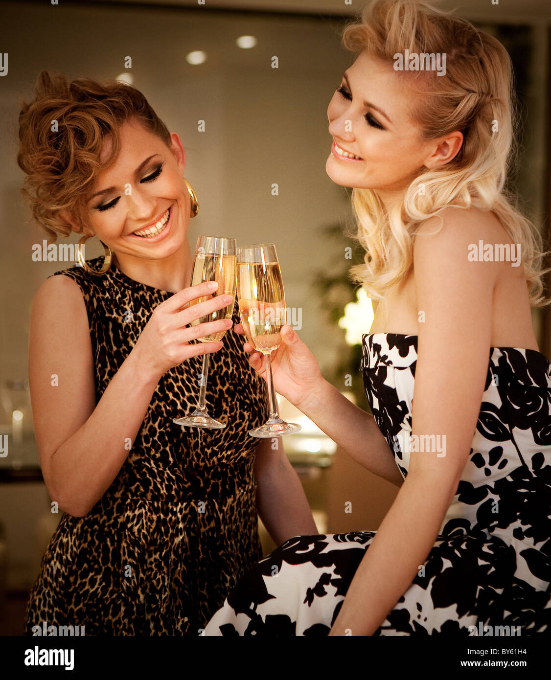 two women drink champagne - Stock Image