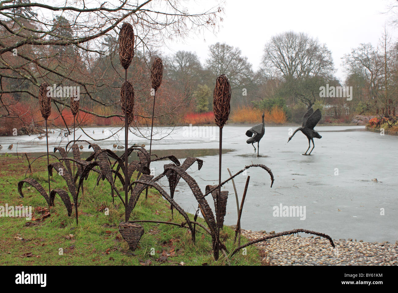 Metal sculptures of reeds and storks, frozen lake in Seven Acres, RHS Garden Wisley, Surrey, England, Great Britain, Stock Photo