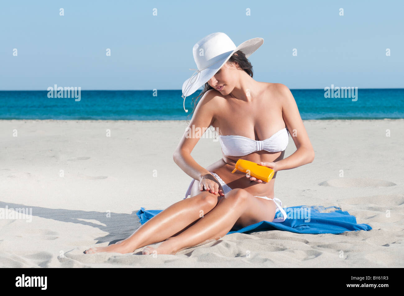 Beautiful young woman applying sun protective lotion before sunbath - Stock Image